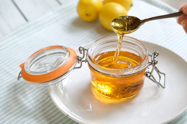 A small jar of golden syrup with lemons in the background