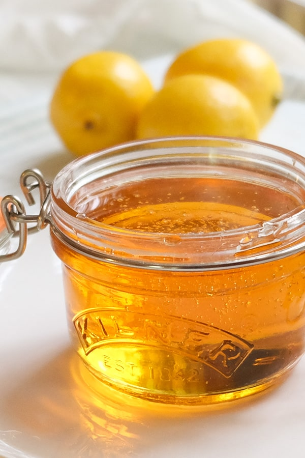 Golden syrup on a small glass jar with lemons in the background