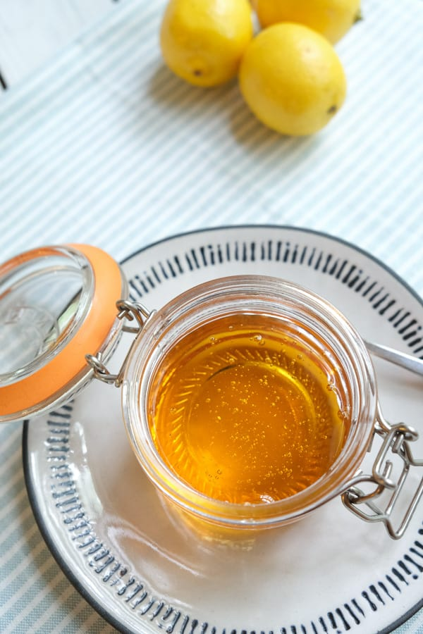 a jar of golden syrup on a plate with spoon