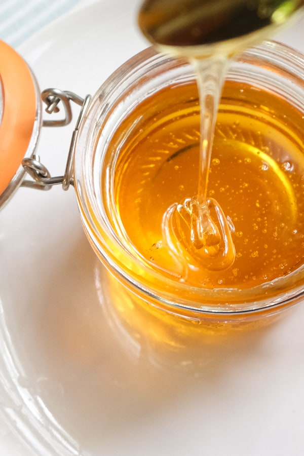 Spoonful of golden syrup drizzling down on a glass jar